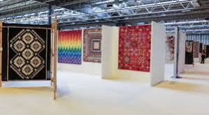 A large room with various quilts hanging