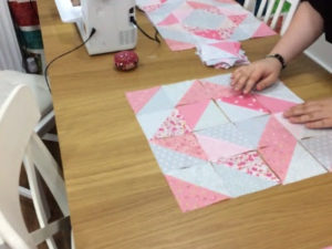 A close up of someone creating half square triangles