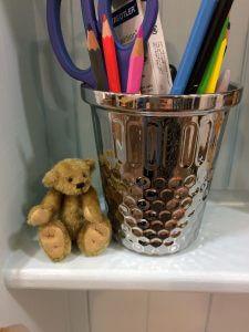 A teddy bear next to a tub of pencils