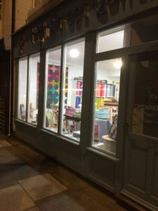 a night-time picture of the outside of the high street quilting shop